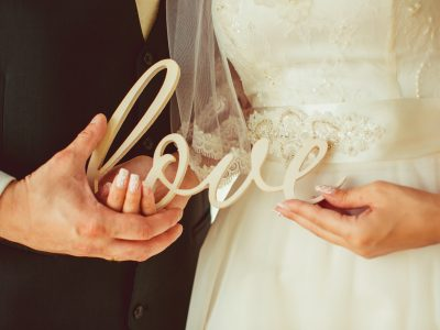 Newlyweds hold in their hands wooden lettering Love